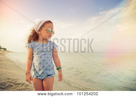 Beautiful little girl with glasses and headscarf on beach, watching the sea.Shallow depth of field. Selective focus.