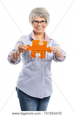 Happy elderly woman holding a puzzle piece, isolated on white background