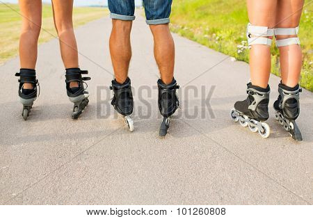 leisure, sport and people concept - close up of legs in rollerskates skating on road from back