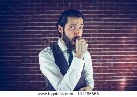 Portrait of man coughing against brick wall
