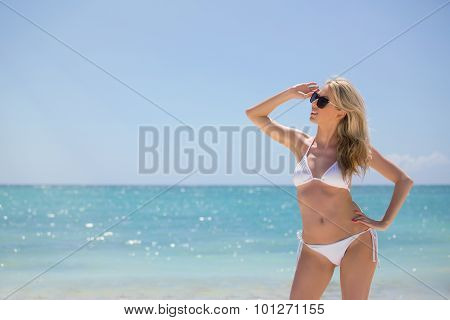Young woman in white bikini on the beach