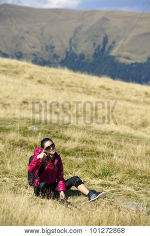 Portrait Of Young Woman Carrying Backpack On The Mountainside And Showing Thumb Up On The Camera