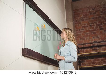 Low angle view of businesswoman holding marker while standing by glass board in creative office