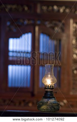 Traditional hurricane lamp placed near the window