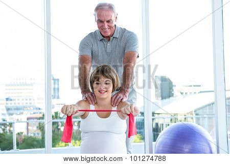 Happy pregnant woman exercising with resistance band while therapist massaging at health club