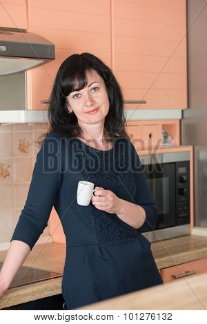 Smiling Woman Drinking  Coffee  At Kitchen
