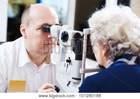 Adult optometry. male optometrist optician doctor examines eyesight of woman patient in eye ophthalmological clinic