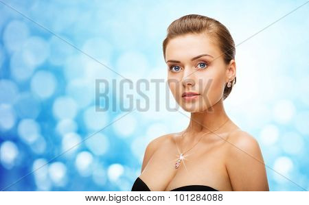 beauty, luxury, people, holidays and jewelry concept - beautiful woman wearing shiny diamond earrings and pendant over blue lights background
