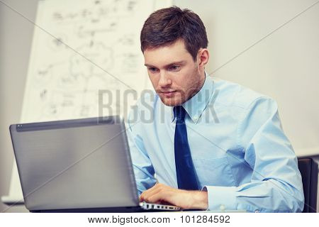 business, people and work concept - businessman sitting with laptop computer in office in front of whiteboard