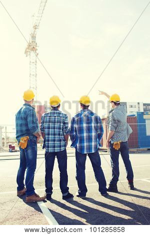 business, building, teamwork and people concept - group of builders in hardhats outdoors from back