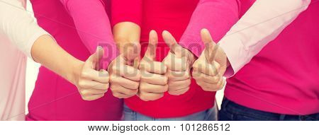 health care, people, gesture, breast cancer awareness and feminism concept - close up of women in pink shirts showing thumbs up