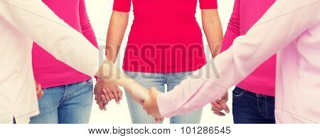healthcare, people, breast cancer awareness and medicine concept - close up of women in pink shirts holding hands over white background