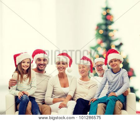 family, happiness, generation, holidays and people concept - happy family in santa helper hats sitting on couch over living room and christmas tree lights background