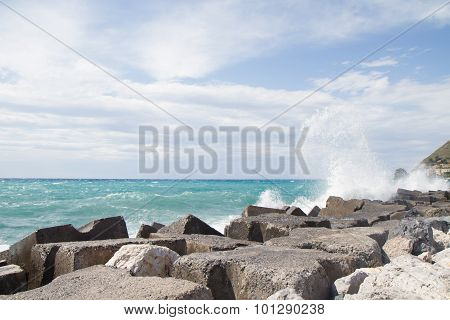 Waves Crashing On The Breakwater In Front Of A Blue Sky