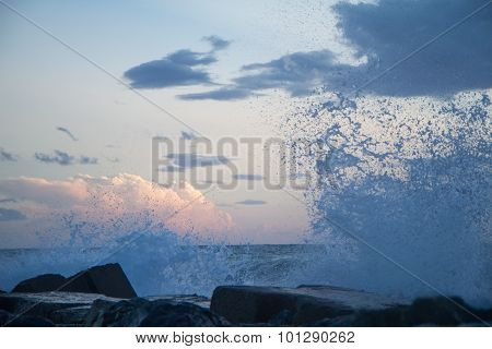 Waves Crashing On The Breakwater In Front Of A Sunset Blue Sky With Clouds
