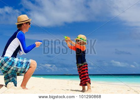 father and son playing with water guns on the beach
