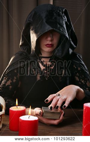 Witch - fortune teller on dark background