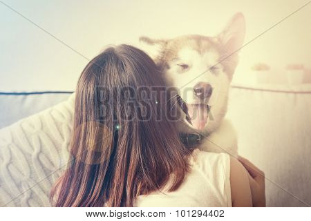 Woman hugging malamute dog in room