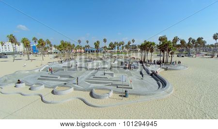 LOS ANGELES - OCT 19, 2014: Many young people ride on skateboards by Skate Park on Venice Beach at sunny day. Aerial view. Skatepark total area is about 16000 sq.ft.