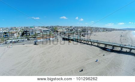 MANHATTAN BEACH - NOV 02, 2014: People walk by Manhattan Beach with long pier at autumn sunny day. Aerial view. Pier is 928 feet long.