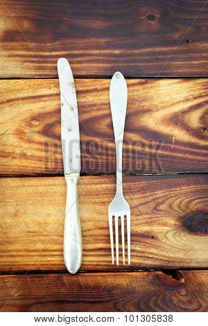 Rusty fork and knife on a burnt wood