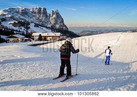 Father And Son Skiing On The Snowy Slopes Of The Alps.