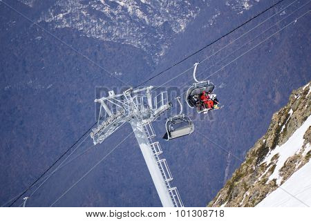 Skiers and snowboarders on a mountain ski lift