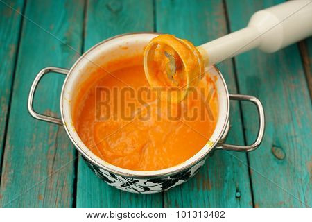 Tasty Creamy Pumpkin Soup Mixed With Blender In White Pot On Turquoise Table