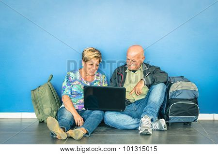 Happy Senior Couple Sitting On The Floor With Laptop Waiting For A Flight At The Airport