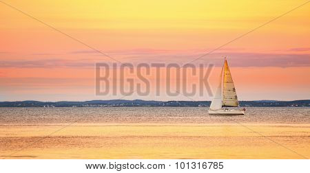 Yacht sailing in the sea at sunset