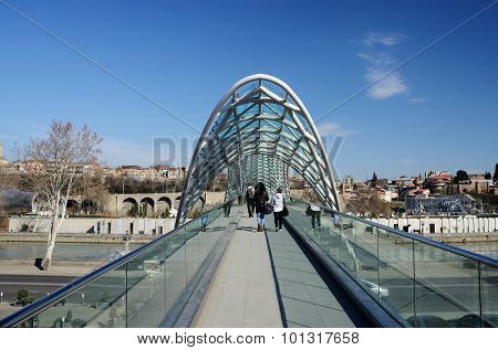People Crossing Modern Futuristic Bridge Of Peace Over Mtkvari River,Tbilisi,Georgia