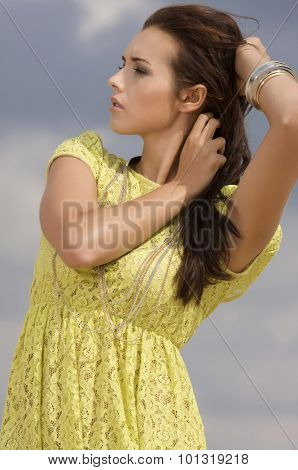 Portrait of a beautiful young adult attractive sensuality and sexy active pretty brunette woman in yellow elegance fashionable dress on background blue sky