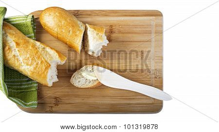 Long baguette and wooden butter knife on wooden cutting board