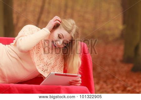 Woman In Fall Park With Tablet Browsing Internet.