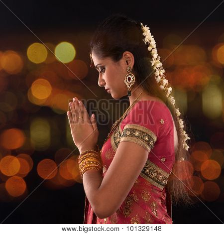 Indian woman in traditional sari praying and celebrating Diwali or deepavali, festival of lights at temple. Female prayer hands folded, beautiful lights bokeh background.