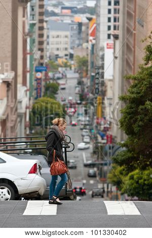 Contemporary Scene Of San Francisco As Woman Crosses Hilly Street