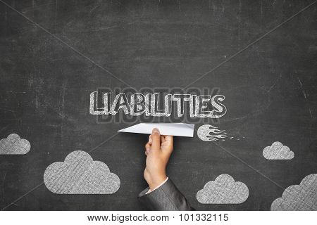 Liabilities concept on blackboard with paper plane