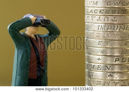Single Miniature Model Looking At English Pound Coins