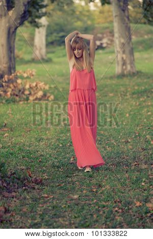young blonde woman in long dress walk in nature among trees, carefree and happy, full body shot, retro colors