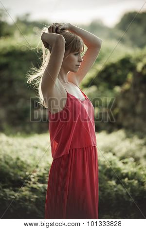 young natural blonde woman portrait wearing elegant red dress outdoor shot , hands in hair