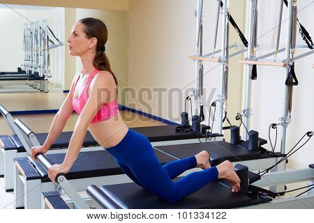 Pilates reformer woman down stretch exercise workout at gym indoor