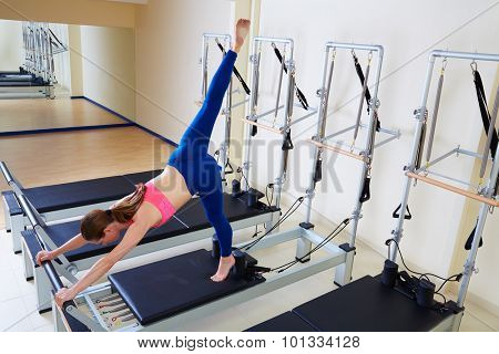 Pilates reformer woman arabesque exercise workout at gym indoor