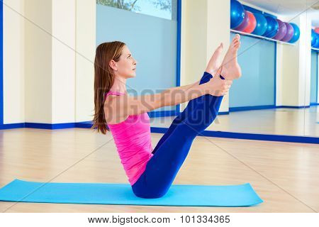 Pilates woman open leg rocker exercise workout at gym indoor
