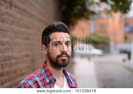 Portrait Of Latin Man Against A Brick Wall.