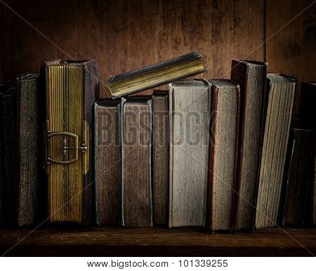 dark image of antique books on wooden shelf.