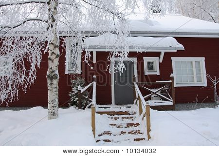 Red Wooden Finnish House In Winter