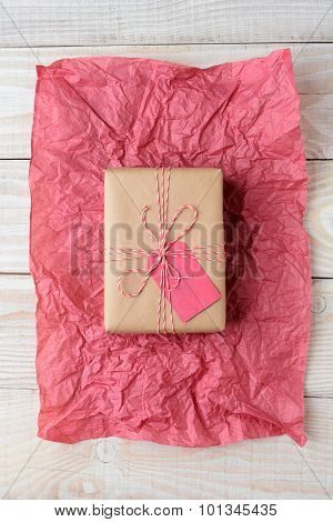 Overhead shot of a plain brown paper wrapped Christmas present on red tissue paper on a rustic wood table. Vertical Format.