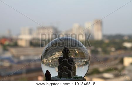 Toy town in snow globe over real city buildings