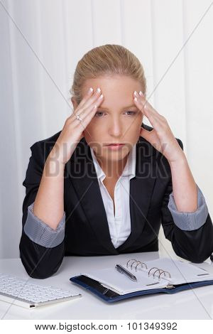 a young woman with migraine and headache sitting in an office.