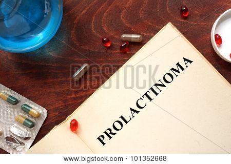 Prolactinoma written on book with tablets.